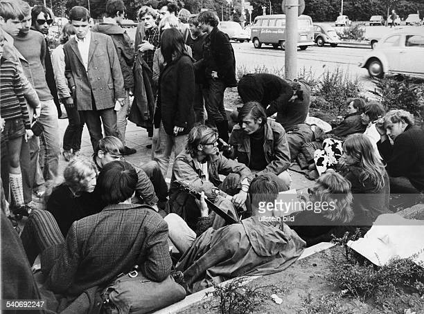 Gammlerversammlung auf der Hamburger Reeperbahn. Die Jugendgruppe hat sich auf den Gehweg neben der befahrenen Straße gesetzt, einer von ihnen spielt...