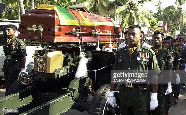 The coffin of Sri lankan army soldier Susantha Chandrakumara is draped with a national flag and taken to a cemetery at Ganemulla just outside the...