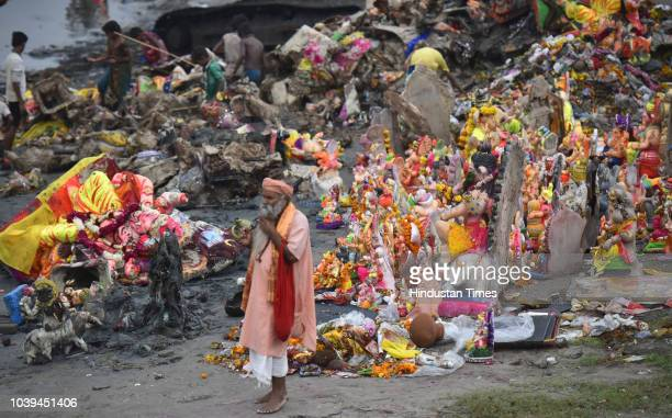Ganesh idols are seen on the banks of the polluted Yamuna river after immersion of the idols on the last day of Ganesh Chaturthi at Kalindi Kunj on...