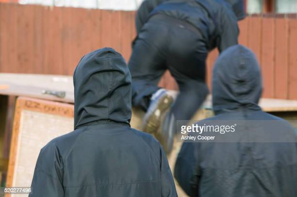 gang dressed in black hoodies - crime stock pictures, royalty-free photos & images
