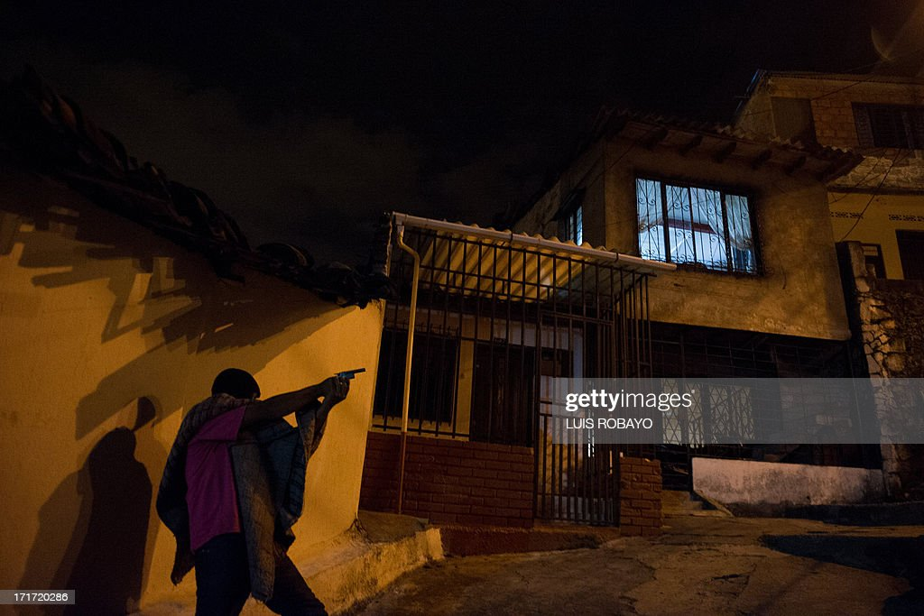 A gang member runs in a hurry after listening gunshots at the Siloe neighborhood in Cali, Colombia on June 27, 2013. Siloe is one of the most dangerous neighborhoods of the city, where more than 20 gangs battle for territories.