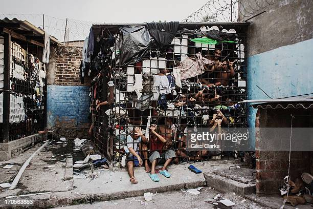 MS13 gang members languish in one of the three 'gang cages' in the Quezaltepeque police station May 20 2013 in San Salvador El Salvador These...