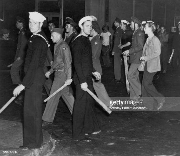 Gangs of American sailors and marines armed with sticks during the Zoot Suit Riots, Los Angeles, California, June 1943. The riots broke out as...