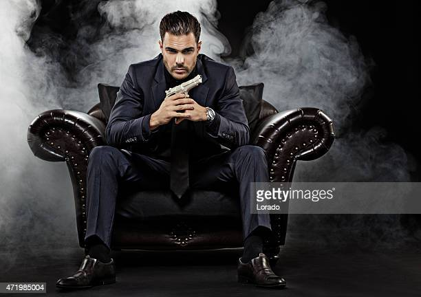gangster holding gun sitting on chair