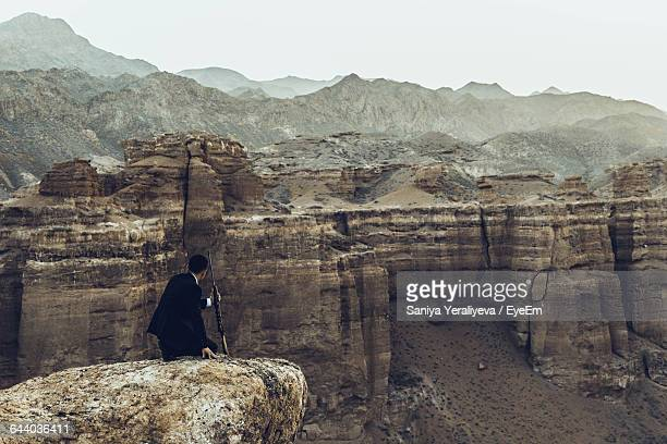 Gangster Kneeling On Rock With Rifle In Canyon Against Sky
