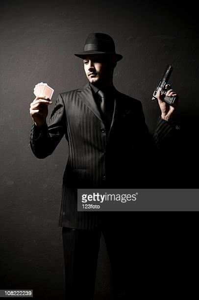 Gangster homme tenant Gun et avoir la main aux cartes