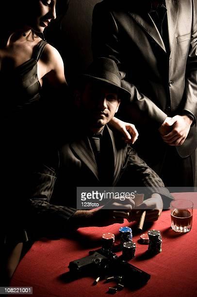Gangster Mann spielt Poker mit Waffe auf Tisch
