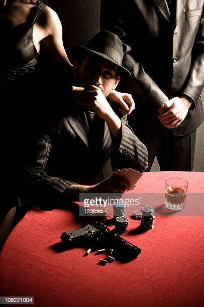 Gangster Man Smoking Cigar and with Gun on Poker Table
