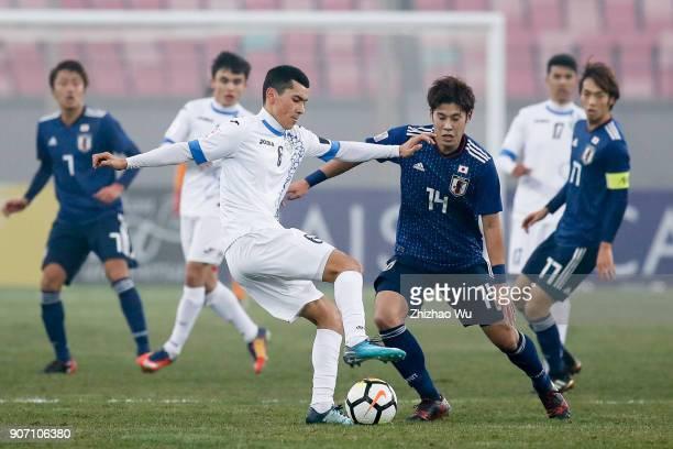 Ganiev Azizjon of Uzbekistan and Takagi Akito of Japan in action during AFC U23 Championship Quarterfinal between Japan and Uzbekistan at Jiangyin...