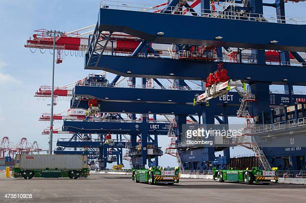 A gantry crane loads containers onto automated guided vehicles during the testing phase of the Long Beach Container Terminal in Middle Harbor at the...