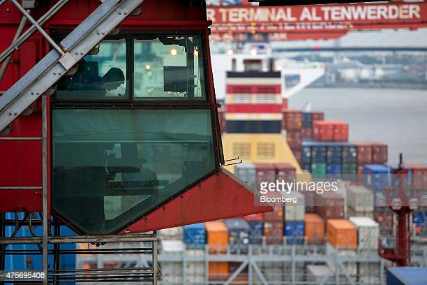 A gantry crane operator loads shipping containers aboard the panamax container ship Antwerpen Express operated by HapagLloyd AG at Hamburger Hafen...