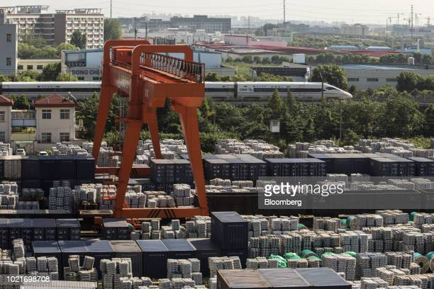 A gantry crane stands as bundles of aluminum ingots sit stacked next to shipping containers at a China National Materials Storage and Transportation...