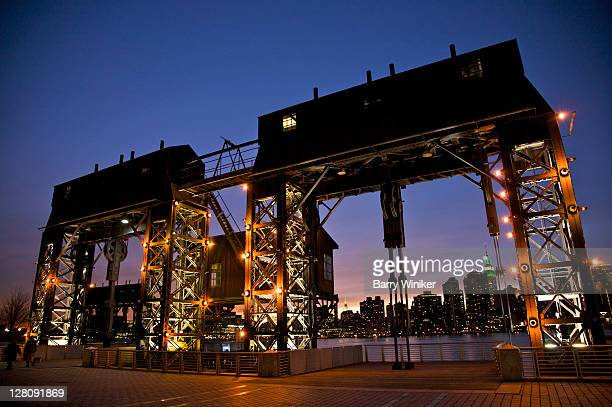 Gantry cranes at dusk, built in 1920s, once used to hoist cargo from ships to waiting railroad cars on the Queens waterfront, Gantry Plaza State Park, opened 1998, Hunter's Point, Long Island City, Queens, New York, U.S.A.