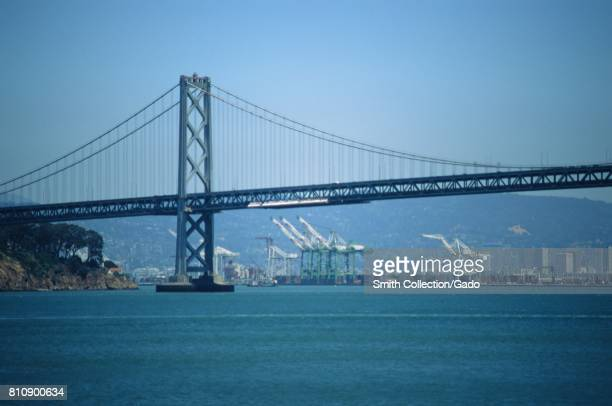 Gantry cranes at the Port of Oakland are visible under the span of the Bay Bridge in the San Francisco Bay San Francisco California June 13 2017