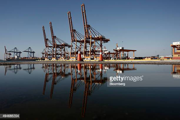 Gantry cranes sit on the dockside at the commercial container section in the Port of Piraeus operated by Piraeus Port Authority SA in Piraeus Greece...