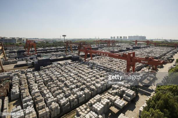 Gantry cranes stand as bundles of aluminum ingots sit stacked at a China National Materials Storage and Transportation Corp stockyard in Wuxi China...
