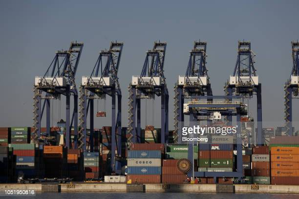 Gantry cranes tower above shipping containers stacked on the dockside at the container terminal operated by Piraeus Container Terminal SA , at the...