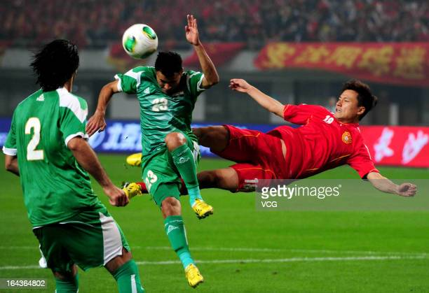 Gao Lin of China and Waleed Salem of Iraq battle for the ball during Asian Cup qualifying match between China and Iraq at Helong Stadium on March 22...