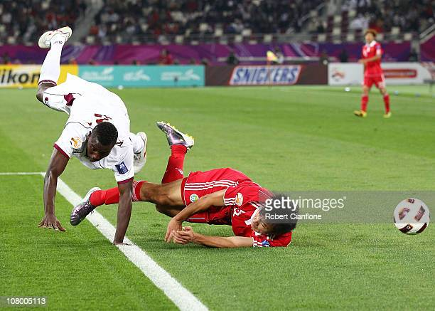 Gao Lin of China is tackled to the ground by Mohammed Kasola of Qatar during the AFC Asian Cup Group A match between China PR and Qatar at Khalifa...