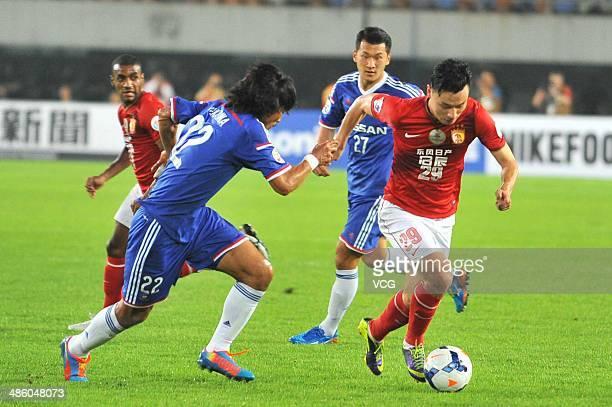 Gao Lin of Guangzhou Evergrande competes for a ball against Yuji Nakazawa of Yokohama F Marinos during the AFC Asian Champions League match between...