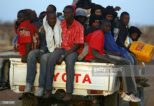 TO GO WITH AFP STORY Illegal immigrants sit at the back of a pick up truck after leaving the city of Gao northern Mali 16 November 2006 on their way...