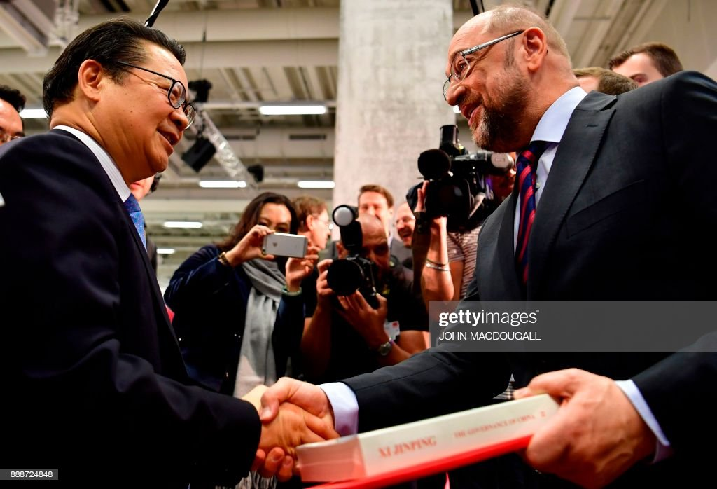 Gao Xuanmin (L), secretary general of the Organization Department of the Central Committee of the Communist Party of China, shakes hands with the leader of the Social Democratic Party (SPD) Martin Schulz (R) as he gives him Chinese leader Xi Jinping's book 'The Governance of China' during the party congress of the SPD on December 9, 2017 in Berlin. Germany's Social Democrats, the country's second strongest party, agreed to kick off exploratory talks with Chancellor Angela Merkel's conservatives that could lead to a new coalition government early next year. / AFP PHOTO / John MACDOUGALL