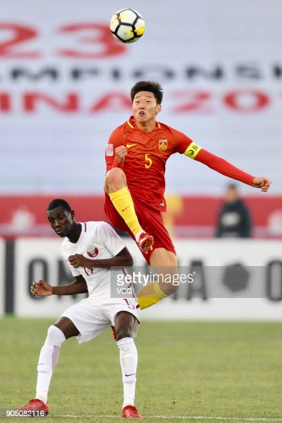 Gao Zhunyi of China and Almoez Ali of Qatar compete for the ball during the AFC U23 Championship Group A match between China and Qatar at Changzhou...
