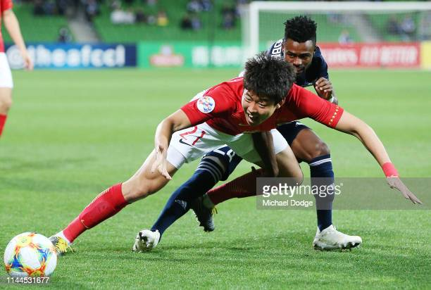 Gao Zhunyi of Guangzhou Evergrande competes for the ball against Elvis Kambosa of the Victory during the round 1 AFC Champions League Group F match...