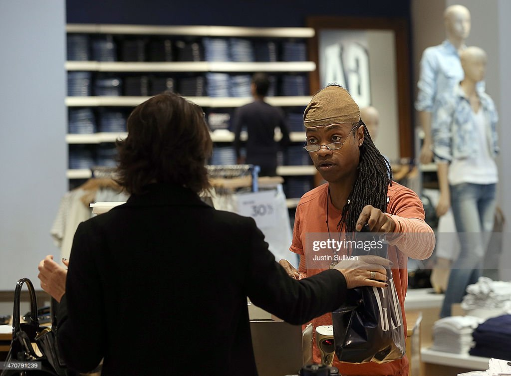 Gap employee Ni'Jean Gibson helps a customer at a Gap store on February 20, 2014 in San Francisco, California. Gap Inc. announced that they will raise their minimum wage for U.S. employees to nine dollars in June of 2014 and to $10 by June of 2015.