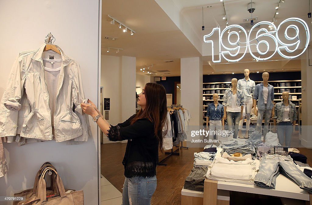 Gap employee Shinju Nozawa-Auclair fixes a clothing display at a Gap store on February 20, 2014 in San Francisco, California. Gap Inc. announced that they will raise their minimum wage for U.S. employees to nine dollars in June of 2014 and to $10 by June of 2015.