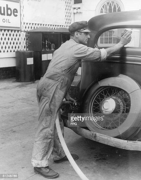 A garage attendant wipes the window of a car whilst filling the tank circa 1935