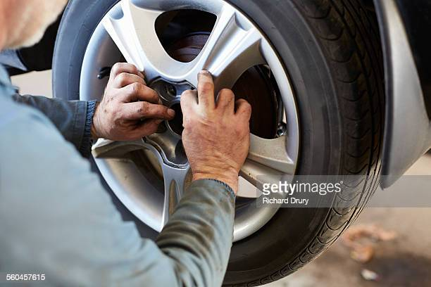 garage mechanic fitting car wheel - wheel stock pictures, royalty-free photos & images