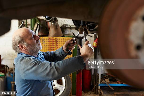 garage mechanic removing anti-roll bar - repair garage stock pictures, royalty-free photos & images