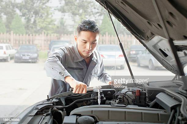 Garage Mechanic Working on Engine