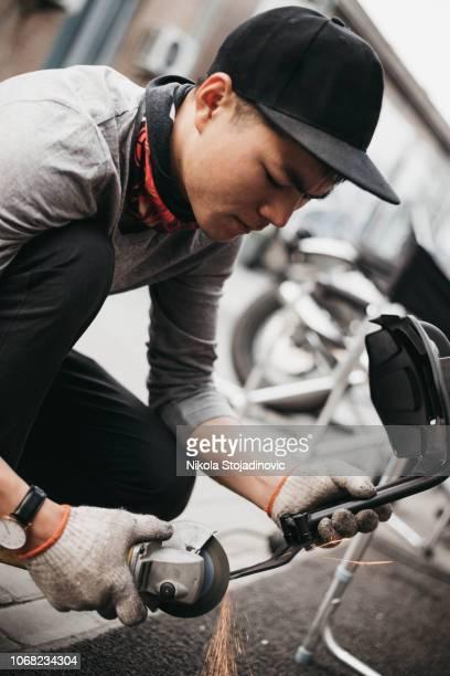 Garage mechanic working on motorcycle in China
