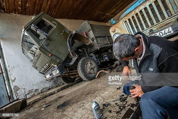 Garage of the Nikitin Kolkhoz at Ivanovka village Azerbaijan Workers prepare trucks for grape harvesting These vehicles deliver grape to Ganja wine...