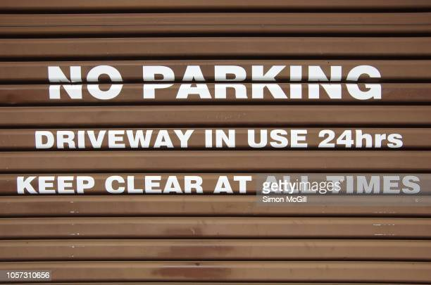 garage roller door with 'no parking: driveway in use 24 hours. keep clear at all times.' - industrial door stock pictures, royalty-free photos & images