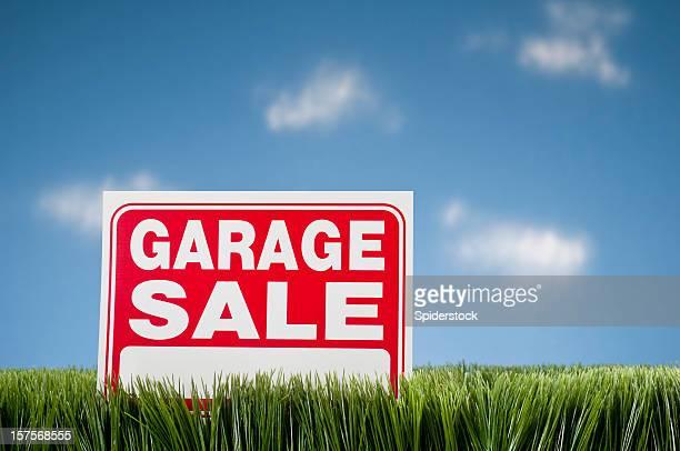 Garage Sale Sign In Grass Against Blue Sky