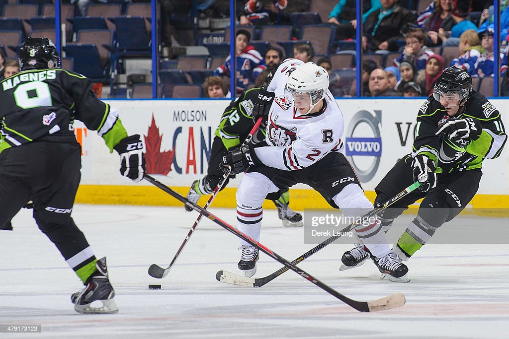 Garan Magnes #9 (L) and Luke Bertolucci #11 of the Edmonton Oil Kings try to check Scott Feser #22 of the Red Deer Rebels during a WHL game at Rexall Place on March 16, 2014 in Edmonton, Alberta, Canada. The Rebels defeated the Oil Kings 5-0.