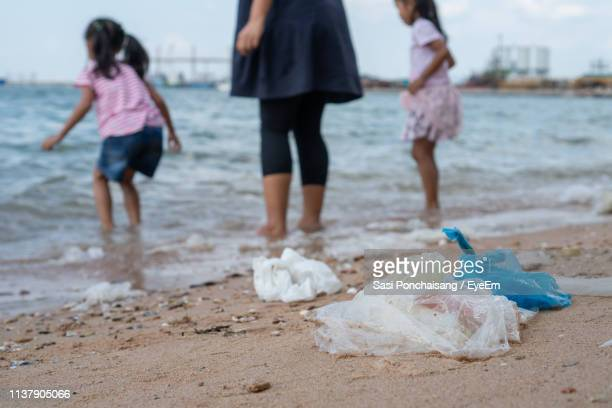 garbage at beach with family in background - plastic bag stock pictures, royalty-free photos & images