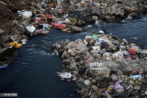 garbage at dirty water - environmental damage stock pictures, royalty-free photos & images
