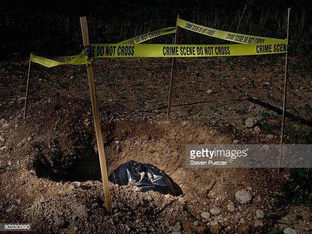 garbage bag in dug hole with crime scene tape - murder stock pictures, royalty-free photos & images