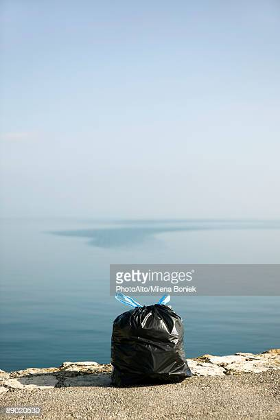 Garbage bag on ledge with sea in background