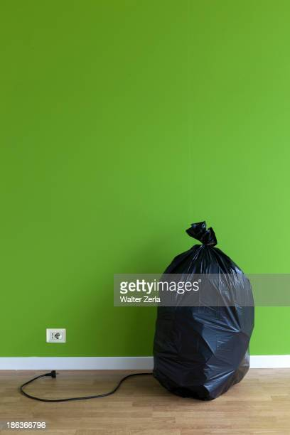 Garbage bag with plug and outlet