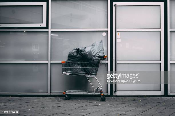 Garbage Bags In Shopping Cart Against Wall