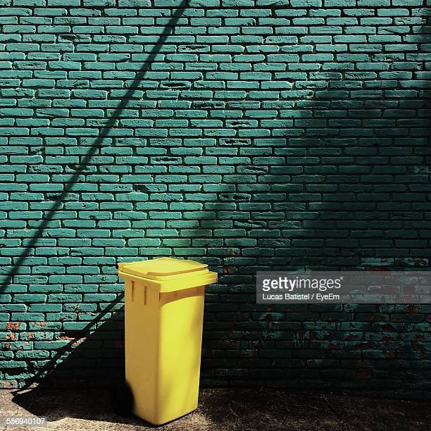 Garbage Bin Against Green Brick Wall