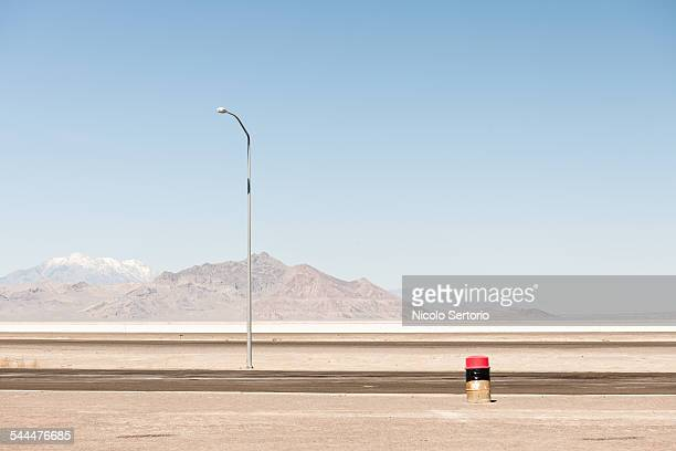 Garbage bin and light in desert with mountains