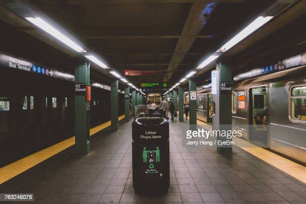 garbage can at illuminated subway station - garbage can stock photos and pictures
