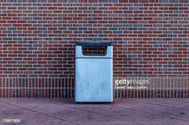 garbage can on walkway against brick wall - garbage can stock photos and pictures