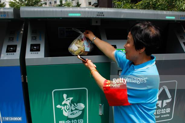 A garbage classification volunteer instructs local residents to sort their garbage at a waste collection point on July 11 2019 in Beijing China...
